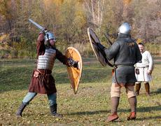 Two warriors in old Russian armors fight with swords and shields - stock photo