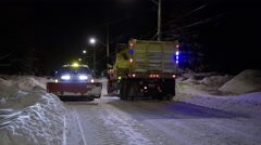 Two snow plows pass each other in the night cleaning up after a blizzard Stock Footage