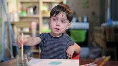 Boy at the table draws with a brush Stock Footage
