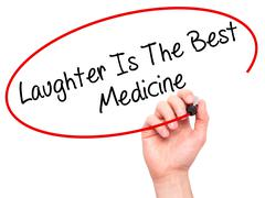 Man Hand writing Laughter Is The Best Medicine  with black marker on visual s - stock photo