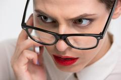 Serious conentrated business woman in glasses talking on cell phone Stock Photos