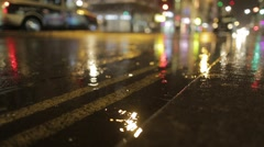 Low Shot of puddle whilst it rains with taxi - stock footage