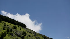 Closeup time lapse of o mountain slope with clouds running in the blue sky. Stock Footage