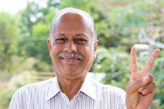 Closeup portrait, joyful elderly gentleman in white striped shirt holding up  Stock Photos