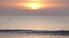 The sun is setting as the calm ocean waves reach the shore Stock Footage