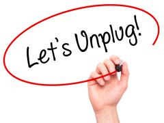 Man Hand writing Let's Unplug! with black marker on visual screen - stock photo