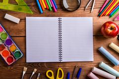 Desk, school supplies, lined paper, wooden background, copy spac Stock Photos