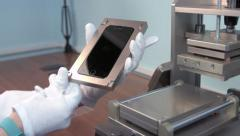 Service worker get smart phone LSD screen from the press after gluing - stock footage