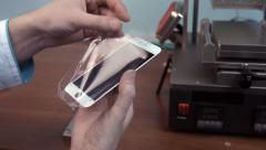 Repairman stick protective film on smartphone screen - stock footage