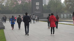 Chinese people walk towards peace monument, Nanjing Massacre memorial Stock Footage