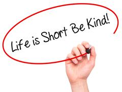 Man Hand writing Life is Short Be Kind! with black marker on visual screen Stock Photos