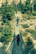 Trekkers crossing a suspension bridge. Stock Photos