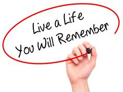 Man Hand writing Live a Life You Will Remember with black marker on visual sc Stock Photos