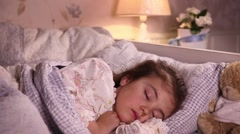 Mother puts her daughter to bed - stock footage