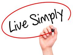 Man Hand writing Live Simply with black marker on visual screen - stock photo