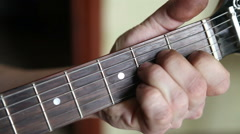 man plays guitar, his fingers on the fretboard closeup - stock footage