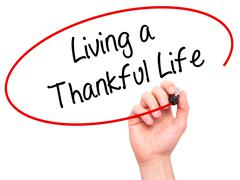 Man Hand writing Living a Thankful Life with black marker on visual screen Stock Photos