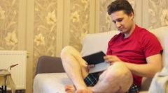 Emotional man playing on a tablet while sitting on a sofa Stock Footage