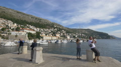 People filming and taking pictures on the stone dock in the Old Port, Dubrovnik Stock Footage