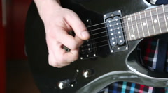 Man playing mediator the electric guitar close-up Stock Footage
