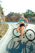 Woman cyclist standing near a bike on a mountain road - stock photo