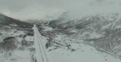 Large Valley with High Mountains in Snow and Icy Road - Aerial - stock footage