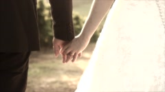 Detail of a married couple walking holding hands on a sunny day. - stock footage