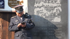 Chinese police officer guard using smartphone in tourist village Stock Footage