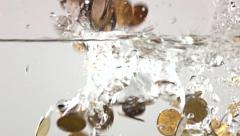Multiple coins sinking in water. Super slow motion shot. Inflation concept - stock footage