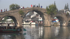 Tourists visit an ancient bridge a renovated water town nearby Shanghai, China - stock footage