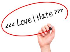 Man Hand writing Love - Hate  with black marker on visual screen - stock photo
