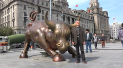 China economy, Chinese tourist poses at massive Shanghai Bund financial bull Stock Footage