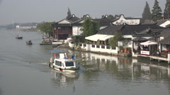 Modern police vessel sails through an ancient (renovated) water town in China - stock footage