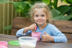 The four-year girl in tea interferes with sugar for breakfast - stock photo