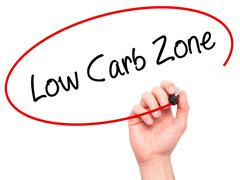 Man Hand writing Low Carb Zone with black marker on visual screen Stock Photos