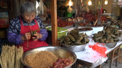 Classic Chinese market, woman prepares popular snack, food street - stock footage