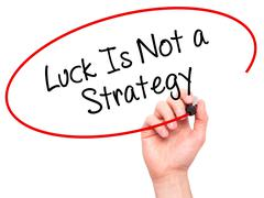 Man Hand writing Luck Is Not a Strategy with black marker on visual screen - stock photo