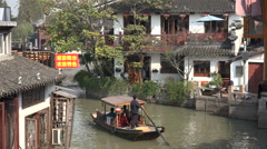 Tourists row through canals of ancient water village in China Stock Footage