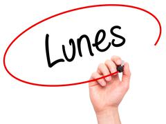 Man Hand writing Lunes (Monday in Spanish) with black marker on visual screen - stock photo
