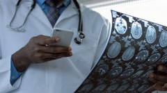 Doctor viewing mri picture and using smart phone Stock Footage
