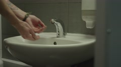 Young man washes his hands and face Stock Footage