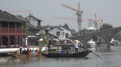 Construction cranes, historic water town, tourist boats, changing China Stock Footage
