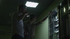 Coworkers choosing food in vending machine at night office building Stock Footage