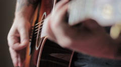 Man with Tatoo playing acoustic guitar - stock footage