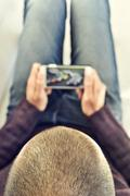 Young man watching a car race in his smartphone Stock Photos
