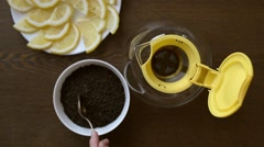 Putting black tea into a teapot - stock footage