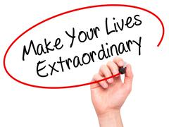 Man Hand writing Make Your Lives Extraordinary with black marker on visual sc Stock Photos