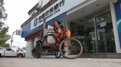 Woman sells sweet potatoes from tricycle,  China Construction Bank office Stock Footage