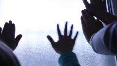 Prisoners POV. Silhouette of childrens hands on the light window. Stock Footage