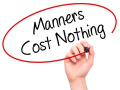 Man Hand writing Manners Cost Nothing with black marker on visual screen - stock photo